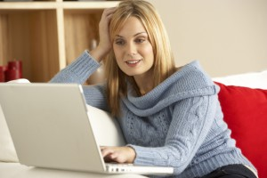 2188712-young-woman-sitting-on-sofa-using-laptop